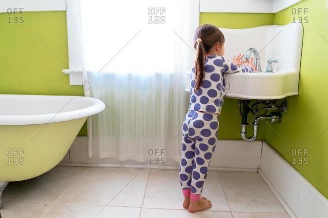 Girl standing in bathroom washing her hands