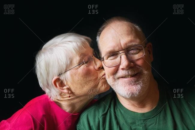 Senior woman kissing cheek of senior man