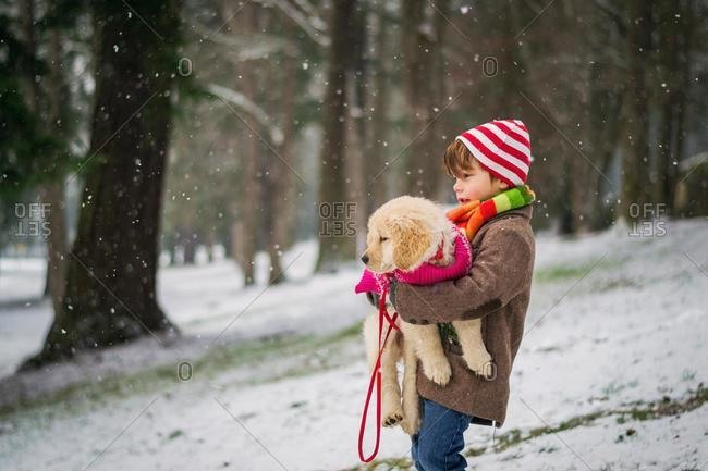 Boy carrying golden retriever puppy dog in snow, USA