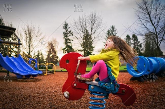 Girl sitting on spring ride in playground, USA