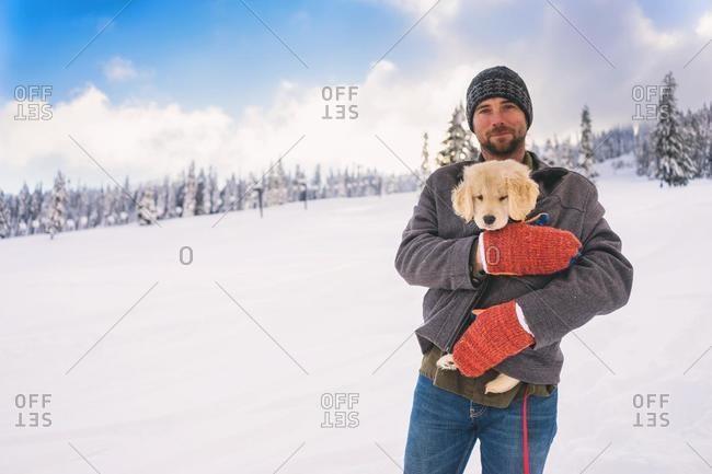 Man keeping a golden retriever puppy warm under his coat, USA