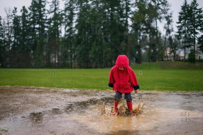 Boy jumping in a puddle in the rain, USA