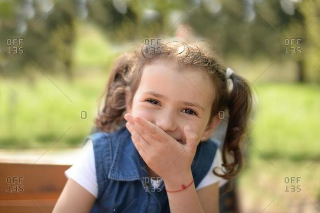 Portrait of Girl holding hand in front of her mouth laughing