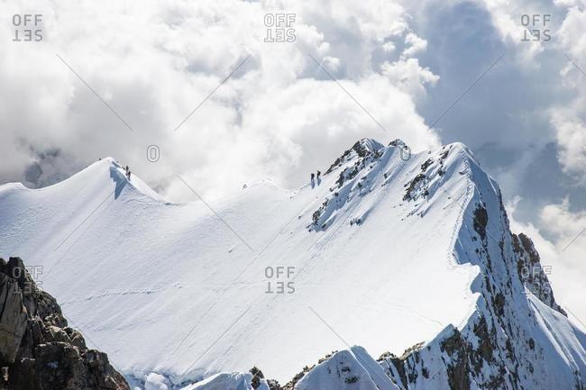 Four People walking along Mountain Ridge in the Swiss Alps, Piz Bernina, Graubunden, Switzerland