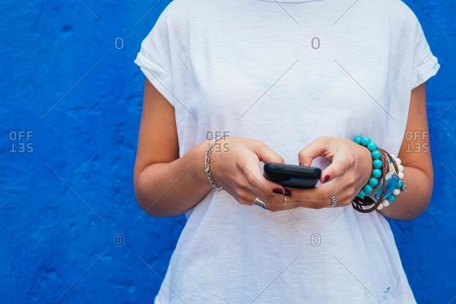 Woman standing by a blue wall using mobile phone