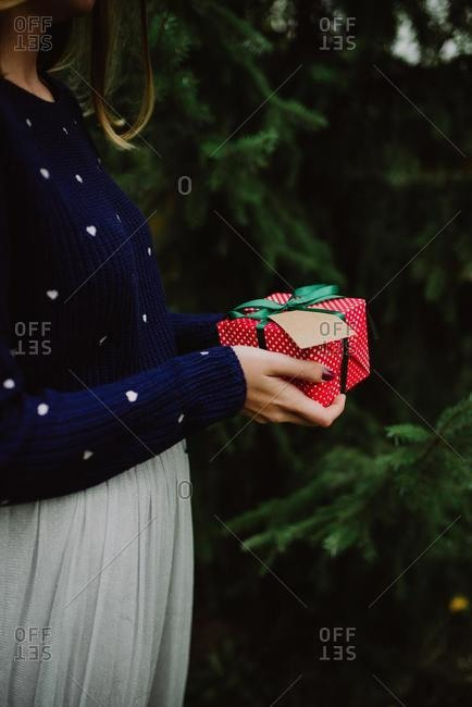 Woman standing next to a fir tree holding a Christmas gift