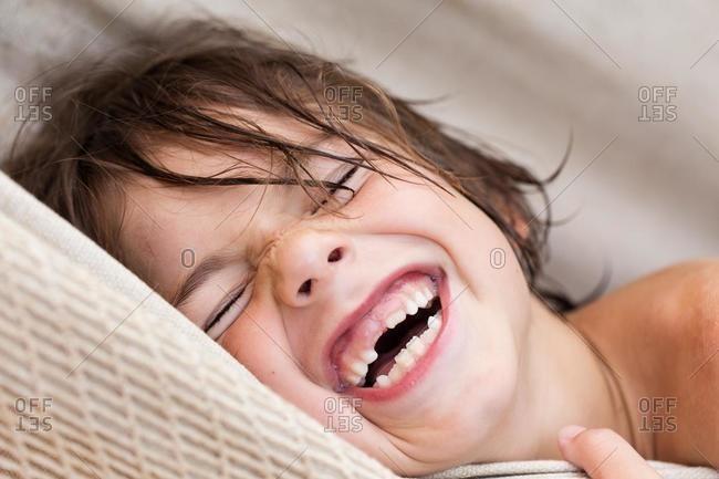 Boy lying in a hammock laughing