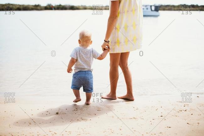 Mother and son at the beach standing at water's edge