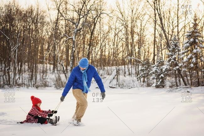 Father pulling daughter on a sled in the snow, USA