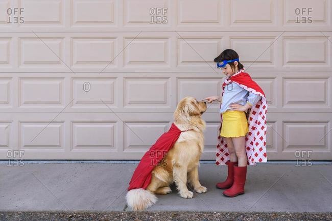 Girl dressed as a superhero standing by the garage with her golden retriever dog