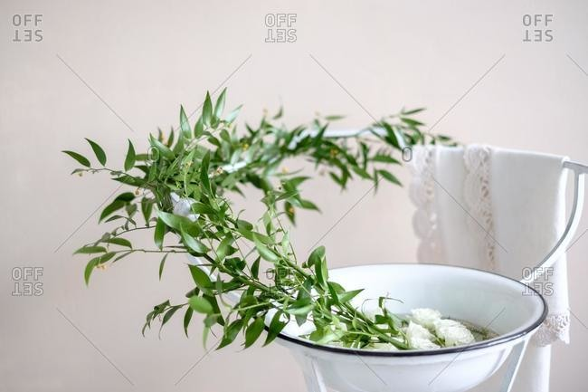 Branches and roses in a  bowl on a metal stand