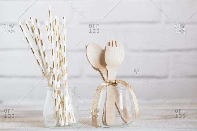Paper drinking straws and wooden cutlery in glass jars
