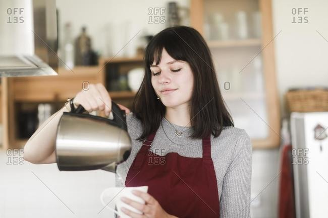 Woman pouring boiling water into a cup