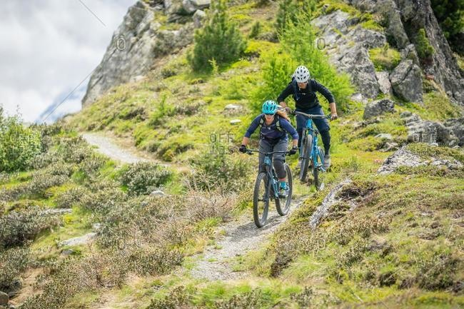 Man and Woman mountain biking in Dolomites, Fanes-Sennes-Braies National Park, Italy