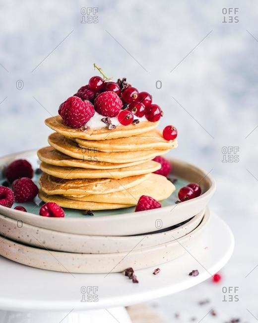 Stack of pancakes with yogurt, fresh raspberries and redcurrants