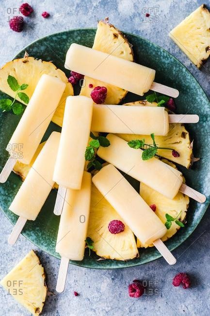 Pineapple ice-lollies with slices of fresh pineapple and raspberries