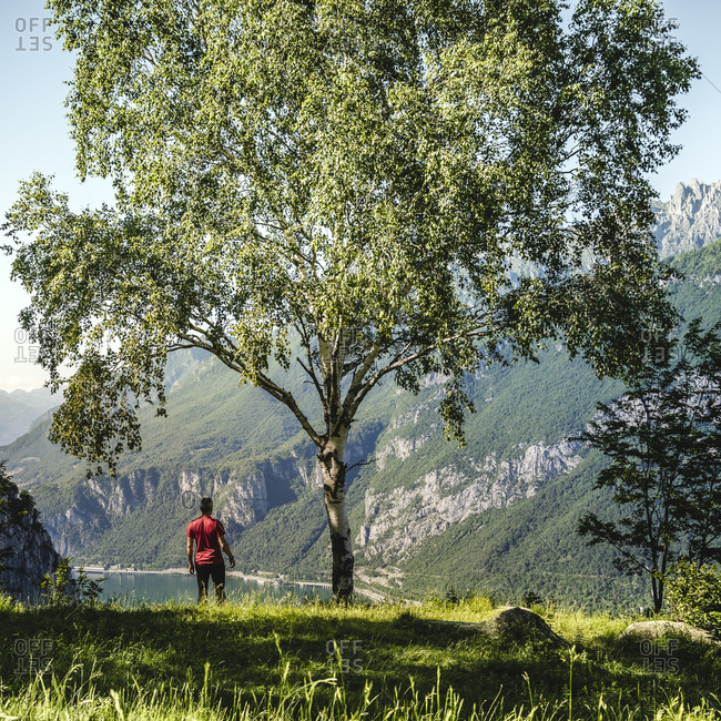 Male hiker looking at view while standing on hill- Lecco- Italy