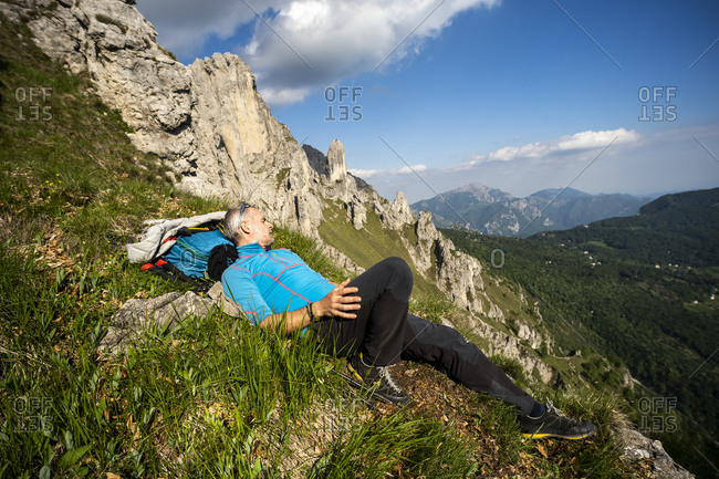 Male hiker lying on Grignetta mountain against sky- European Alps- Lecco- Italy