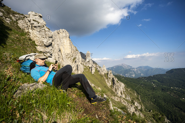 Man lying on Grignetta mountain against sky- European Alps- Lecco- Italy