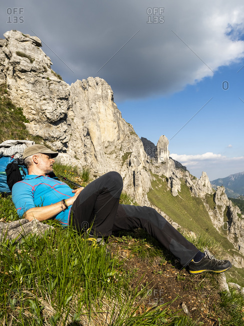 Mature man lying on Grignetta mountain against sky- European Alps- Lecco- Italy