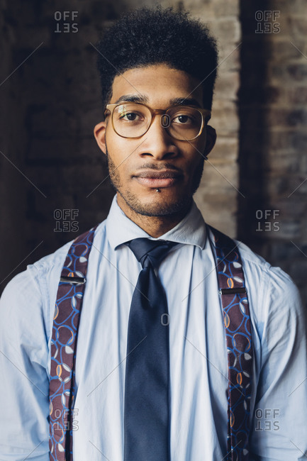 Portrait of a stylish young man wearing shirt- tie and suspenders