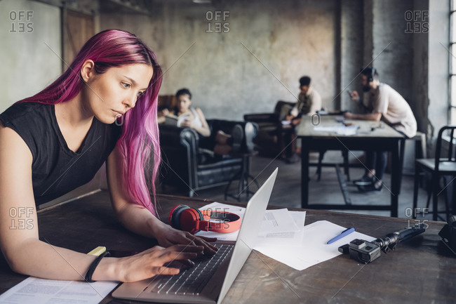 Creative businesswoman with pink hair using laptop in loft office