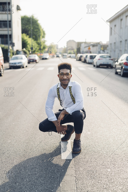 Portrait of a confident stylish young man crouching on the street in the city