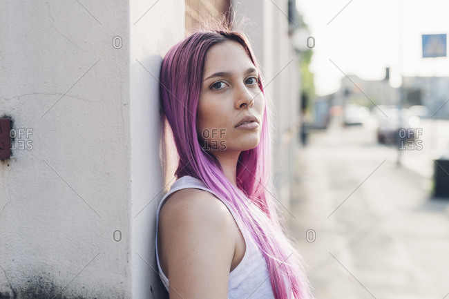 Portrait of a stylish young woman with pink hair leaning against a wall in the city