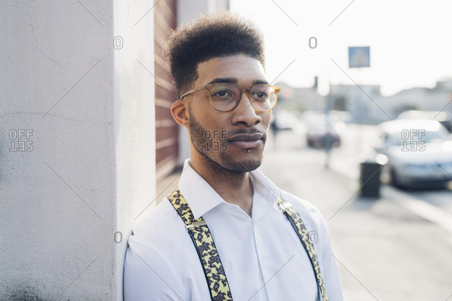 Portrait of a confident stylish young man leaning against a wall in the city