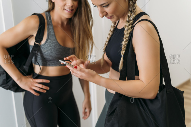 Two sporty women using smartphone at health club
