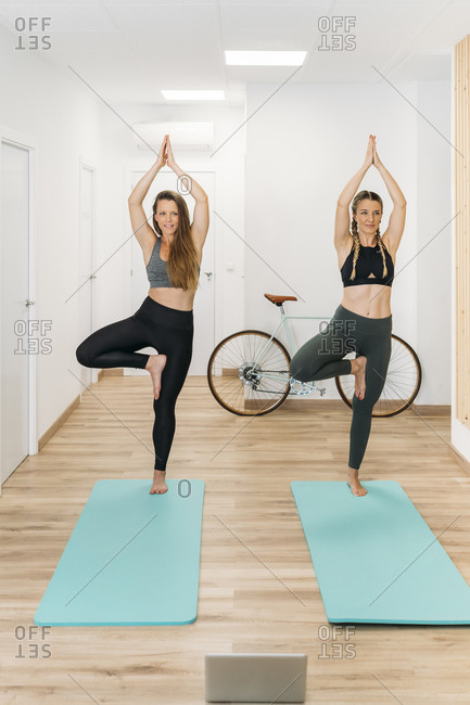 Two sporty women having an online yoga course at health club