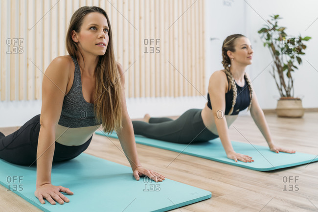 Two sporty women exercising at health club