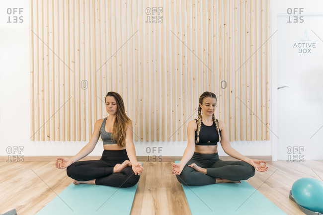 Two sporty women practicing yoga at health club