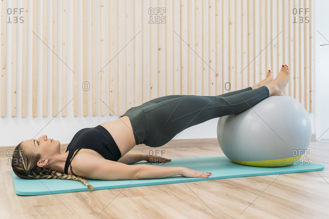 Woman exercising with fitness ball at health club
