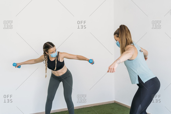Woman wearing face mask exercising with coach at health club