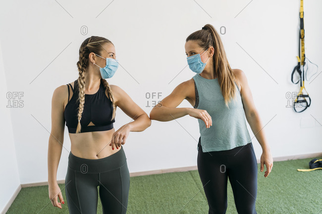 Two sporty women wearing face masks giving elbow bump at health club