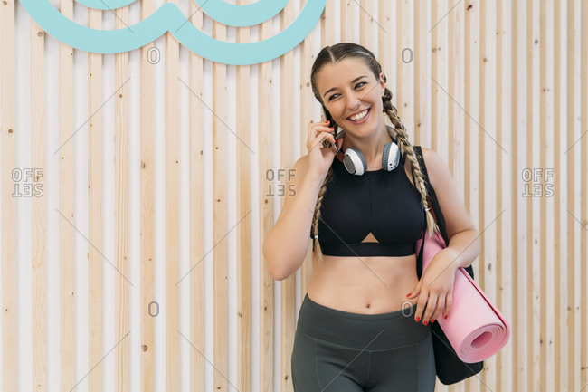 Sporty woman on the phone at health club