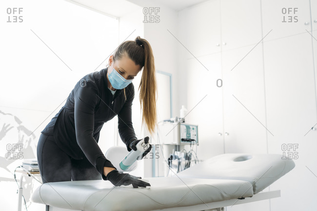 Woman wearing face mask disinfecting lounge in examination room