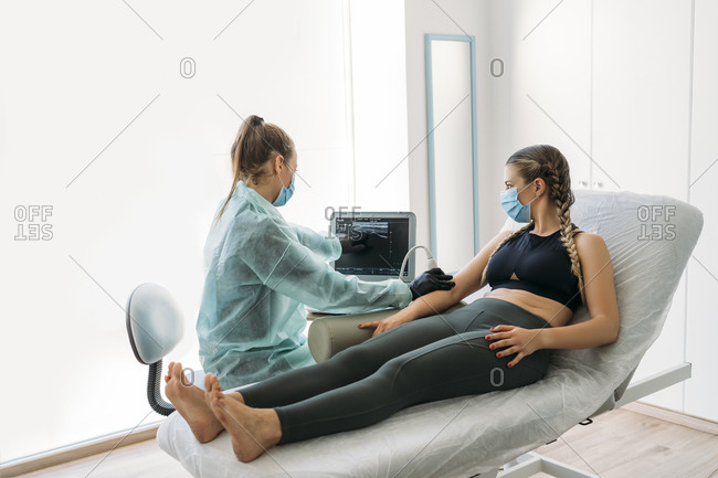 Doctor wearing face mask examining sportswoman with ultrasound scanner