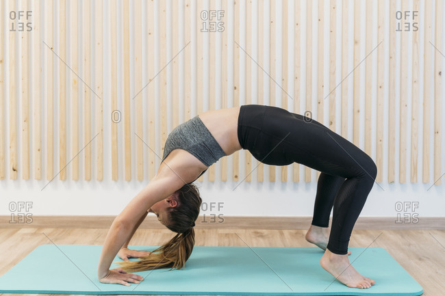 Woman in bridge position exercising in health club