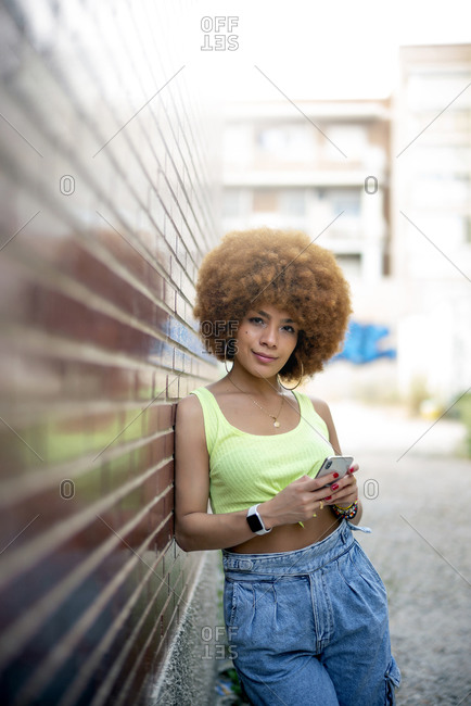 Mid adult woman with afro hair using smart phone while leaning on brick wall in city