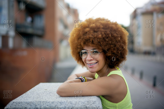 Close-up of smiling woman with afro hair standing by retaining wall in city