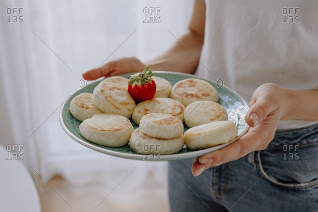 close-up of mid adult woman holding cheesecakes with strawberry in plate at home