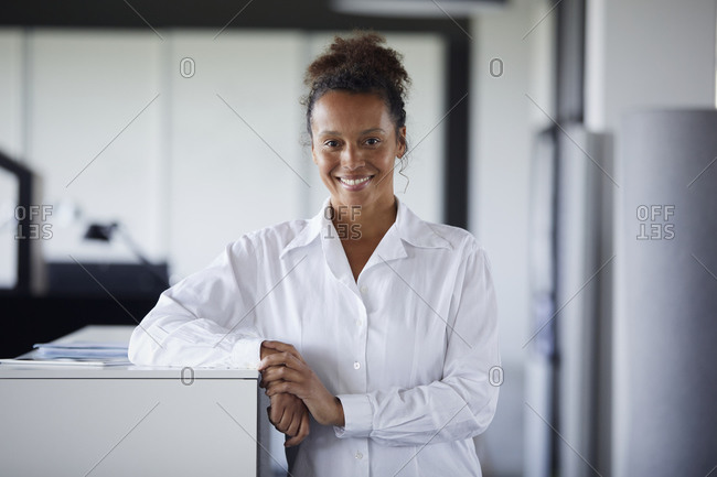 Portrait of smiling businesswoman leaning on counter in modern office