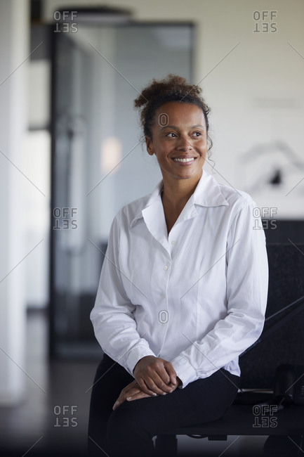 Portrait of smiling businesswoman in modern office looking at distance