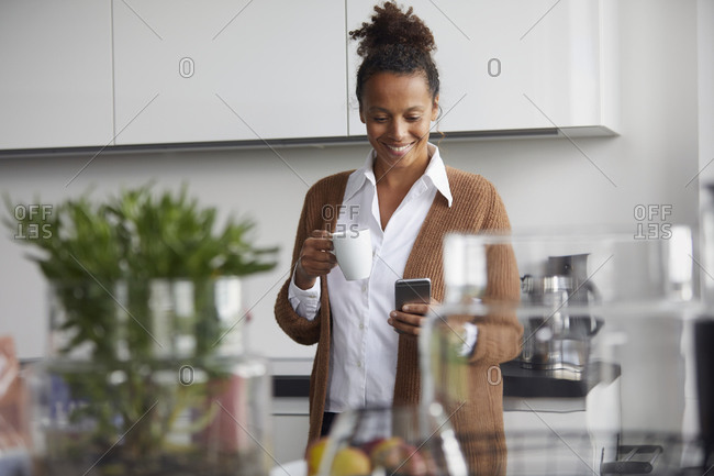 Portrait of smiling businesswoman standing in kitchen with cup of coffee looking at mobile phone