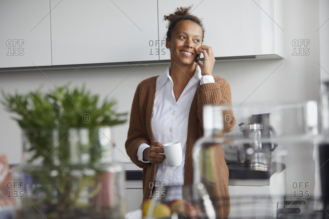 Portrait of smiling businesswoman on the phone standing in kitchen with cup of coffee looking at distance