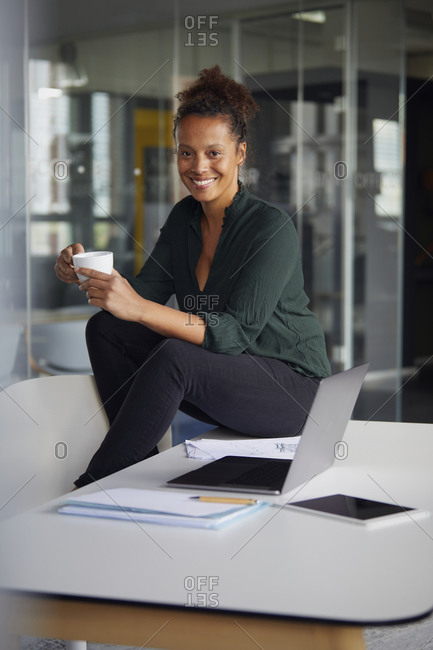 Portrait of smiling businesswoman sitting on desk with cup of coffee having a break