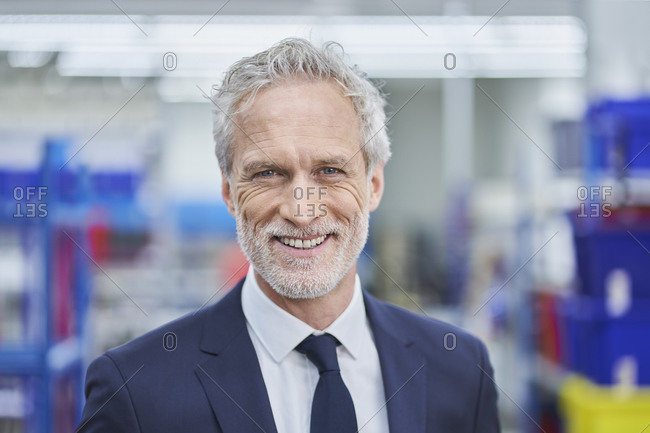 Happy mature male manager in factory