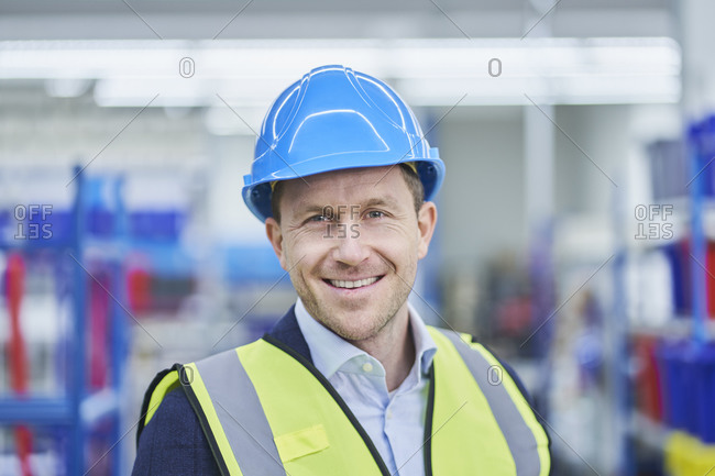Happy male supervisor wearing hardhat and reflective clothing in factory